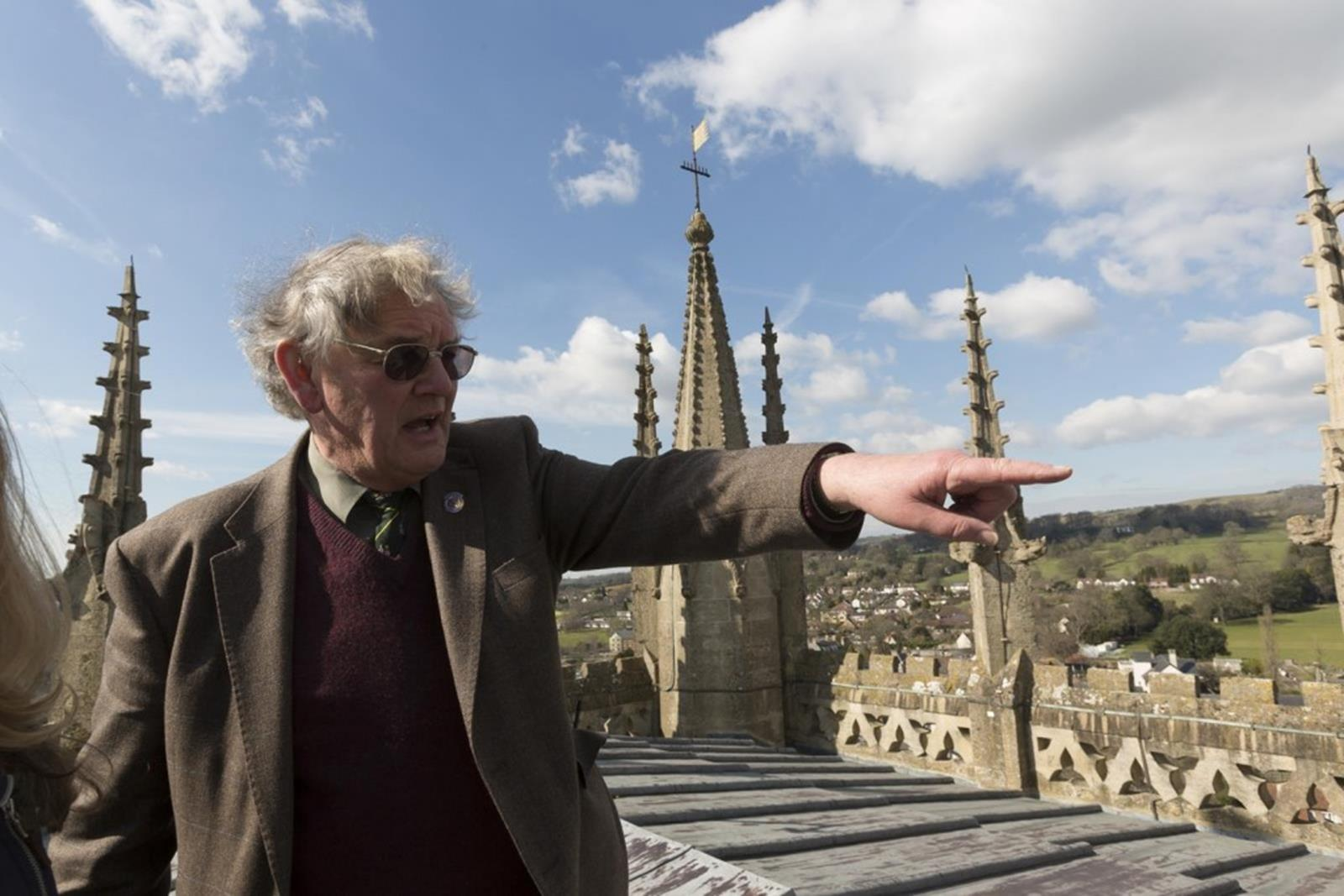 A man points out the views from the top of Wells Cathedral