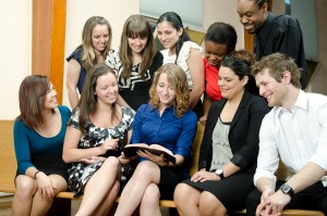 A group of young adults gathered around a Bible